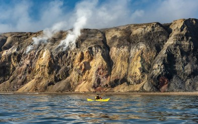 Person in yellow kayak in front of smoking hills.