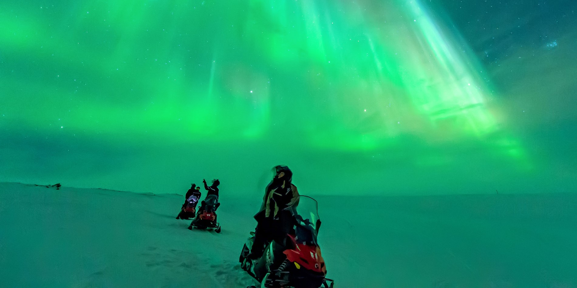Three snowmobiles and drivers looking up at the northern lights.